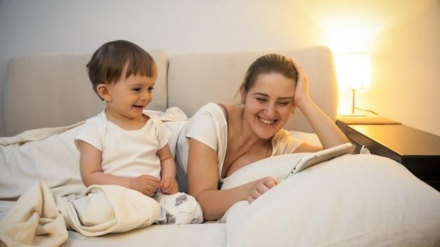 ベッドで母親と横になって、デジタルタブレットコンピューターでビデオを見ているかわいい男の子の肖像画。