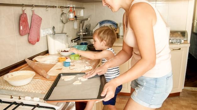 부엌에서 베이킹 팬에 쿠키를 굽고 젊은 어머니와 함께 귀여운 어린 소년의 초상화