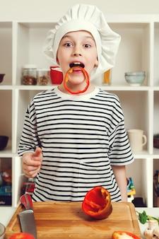 부엌에서 즐거운 시간을 보내는 귀여운 요리사의 초상화. 요리사 모자를 쓴 소년. 미래의 직업을 꿈꾸는 아이. 집에서 부엌에서 샐러드를 위해 후추를 자르는 요리사