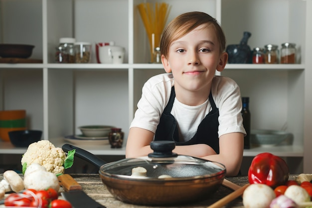 부엌에서 귀여운 작은 요리사의 초상화입니다. 앞치마를 입은 소년. 미래의 직업을 꿈꾸는 아이. 집에서 주방에서 새로운 요리법을 시도하는 요리사. 요리 교실에서 소년입니다.
