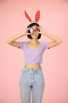 スタジオでピンク色の背景にイースターエッグを保持しているかわいい女の子の肖像画。キリストの宗教の最も重要な日の一つ。イエスの復活を思い出すため。 Premium写真