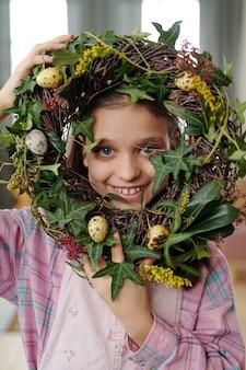 계란과 함께 꽃 화환을 들고 카메라를 보며 웃고 있는 귀여운 소녀의 초상화