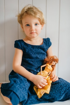 귀여운 소녀의 초상화는 그녀의 사랑스러운 바비를 보유하고 흰 벽 위에 포즈