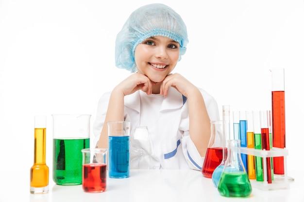 白い壁に隔離された試験管内の色とりどりの液体で化学実験を行う白い白衣のかわいい女の子の肖像画