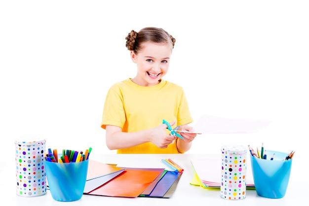 Портрет милой маленькой девочки в желтой футболке режет картон ножницами - изолированный на белизне.