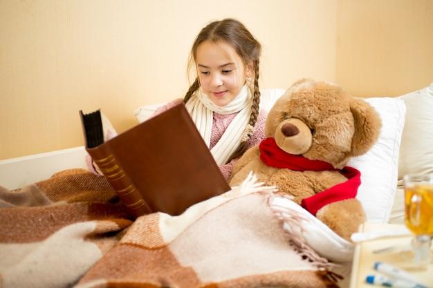 ベッドに横たわって、テディベアに本を読んでいるかわいい女の子の肖像画