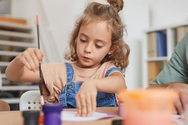 Портрет милой маленькой девочки, которая рисует картины, наслаждаясь уроком искусства и ремесла в школе или центре развития