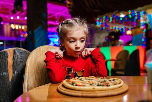 Портрет милой маленькой девочки, сидящей за обеденным столом и едящей пиццу Premium Фотографии