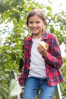 Портрет милой маленькой девочки, сидящей на стремянке в саду и держащей свежее яблоко