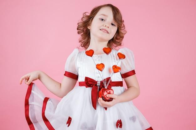 スタジオでピンクのドーナツまたはガラスのハートと白いドレスに立っているかわいい女の子の肖像画
