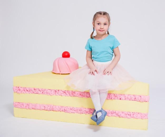 白い背景の上の大きなケーキとかわいい女の子の肖像画