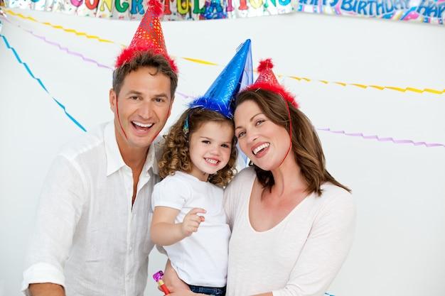 Портрет милой маленькой девочки с родителями в день рождения