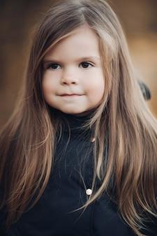 긴 머리와 개암 눈 매체를 가진 귀여운 어린 소녀의 초상화를 닫습니다. 완벽한 피부와 평온한 감정을 가진 자연스러운 아름다움을 가진 여자 아이의 사랑스러운 얼굴