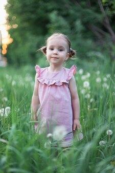 ルピナスの花のフィールドにかわいい小さな幸せな2歳の女の子の肖像画