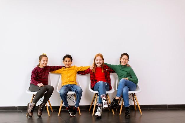 Портрет милых маленьких детей в джинсах, сидящих на стульях у белой стены