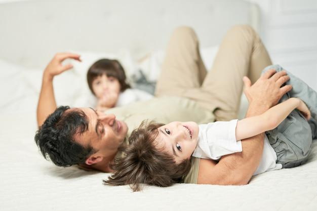 그의 아버지와 형제 자매와 함께 놀면서 집에서 침대에 함께 누워있는 동안 카메라를 보고 웃고 있는 귀여운 라틴 소년의 초상화. 행복한 어린 시절, 부모 개념. 선택적 초점