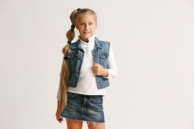 카메라를보고 흰색 스튜디오 벽에 웃 고 세련 된 청바지 옷에 귀여운 작은 십 대 소녀의 초상화. 키즈 패션 컨셉