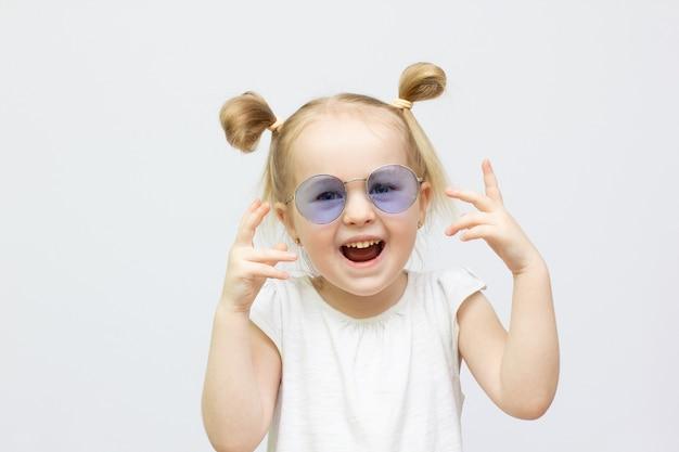 サングラスでかわいい幼児の女の子の肖像画。口を開けて楽しんでいる子供は白い背景で隔離。カメラを見てください。うわー変な顔