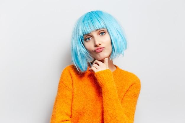흰 벽에 키스를 불고 보내는 주황색 스웨터에 파란 머리를 가진 귀여운 사랑스러운 여자의 초상화.