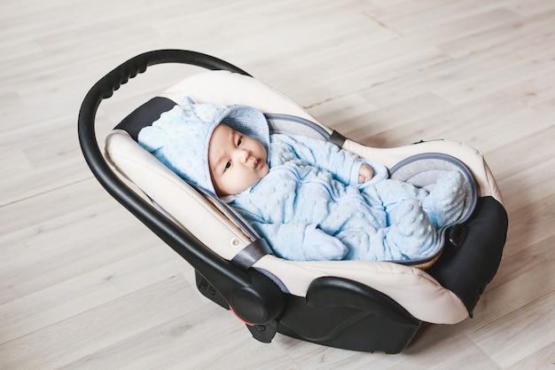 자동차 좌석에 앉아 귀여운 혼혈 아기의 초상화. 어린이 운송 안전