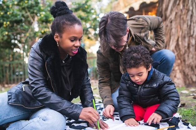 야외 공원에서 함께 좋은 시간을 보내고 귀여운 혼혈 민족 가족의 초상화.