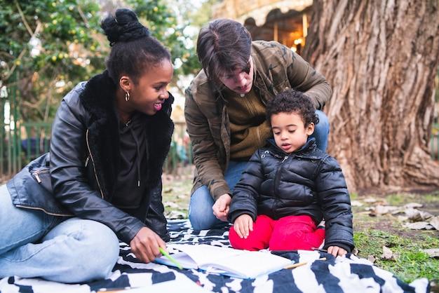 屋外の公園で一緒に楽しい時間を過ごしているかわいい混血民族家族の肖像画。