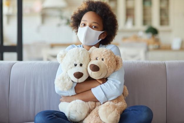 見ている保護フェイスマスクを身に着けているカジュアルな服を着たかわいい混血の十代の少女の肖像画