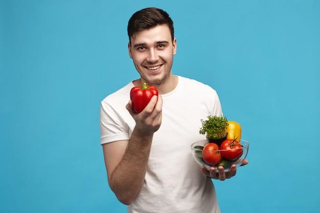 Портрет симпатичного мускулистого темноволосого молодого кавказского человека в белой футболке