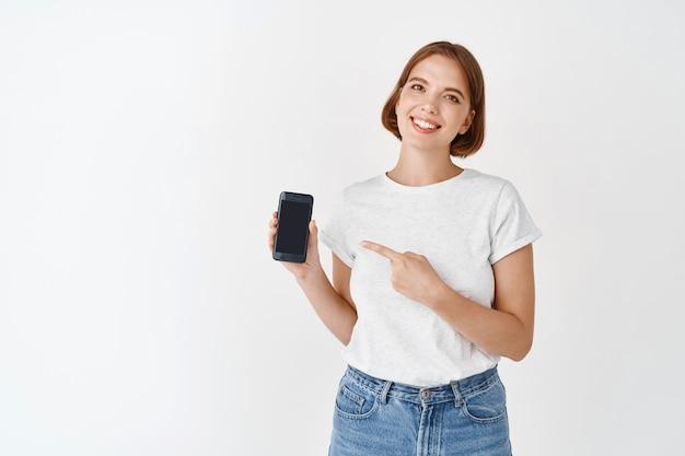 Портрет милой естественной девушки улыбается, указывая пальцем на экран смартфона. женщина показывает приложение на дисплее, в джинсах с футболкой, белая стена