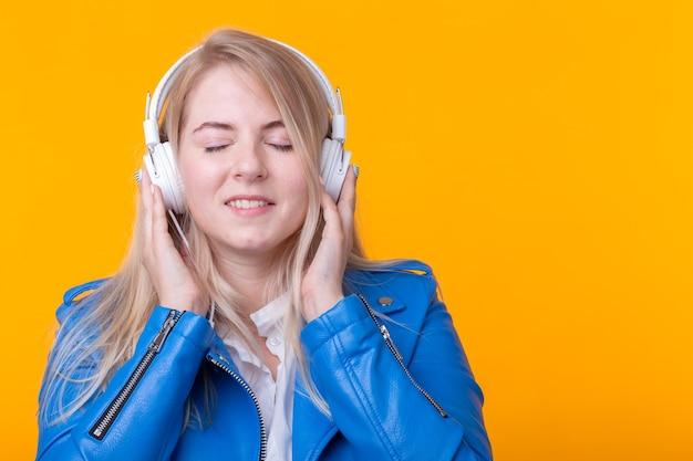 파란색 헤드폰에서 좋아하는 음악을 듣고 귀여운 긍정적 인 젊은 금발 소녀의 초상화