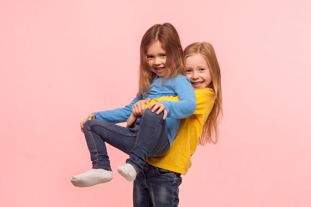귀여운 취학 전 소녀의 초상화는 여동생을 들어올리고 웃고, 친구들이 함께 즐겁게 놀고, 게임을 하고, 평온한 유치한 행복을 표현합니다. 분홍색 배경에 고립 된 스튜디오 촬영
