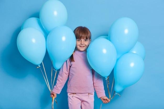 風船で青い壁にポーズをとってかわいい未就学児の肖像画