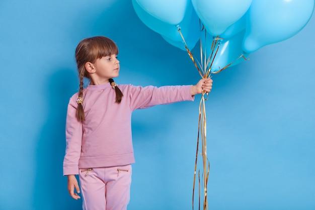 Портрет милого дошкольника позирует на синей стене с воздушными шарами