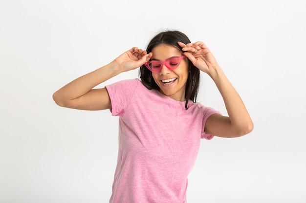 Портрет милой довольно улыбающейся эмоциональной женщины в розовой рубашке и стильных солнцезащитных очках, изолированные на белом фоне