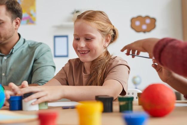 Портрет милой рыжеволосой девушки рисует картины, наслаждаясь уроком искусства и ремесла в школе или центре развития