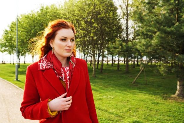 공원에서 빨간 코트에 귀여운 redhaired 여자의 초상화