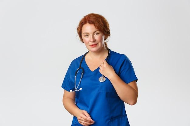 かわいい赤毛の女性医師、看護師または青いスクラブで医師の肖像画は聴診器で患者をチェックし、人々を治療し、クリニックでの発生中にコロナウイルスと戦っています。
