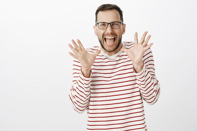 Портрет милого испуганного взрослого парня-гея в очках, кричащего от страха и держащего поднятые ладони перед лицом, видящего что-то шокирующее и пугающее