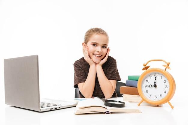 白い壁に隔離されたクラスで本を勉強して読んでいる間銀のラップトップを使用してかわいい女子高生の肖像画