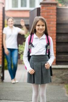 家の前に立っているかわいい女子高生の肖像画。戸口に立って手を振っている母親