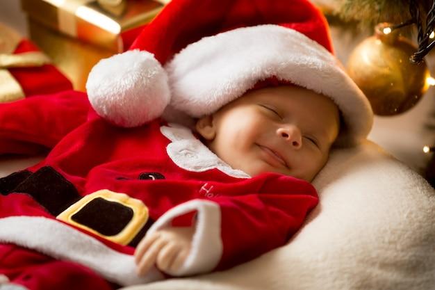 Портрет милого улыбающегося мальчика в костюме санта-клауса и шляпе