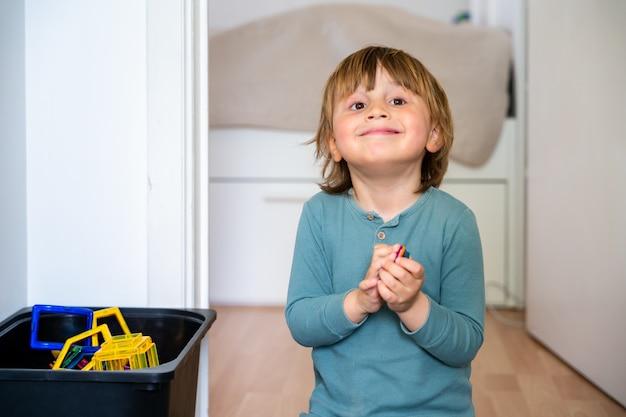Портрет милого улыбающегося мальчика трех лет сидит на полу и играет с магнитными блоками
