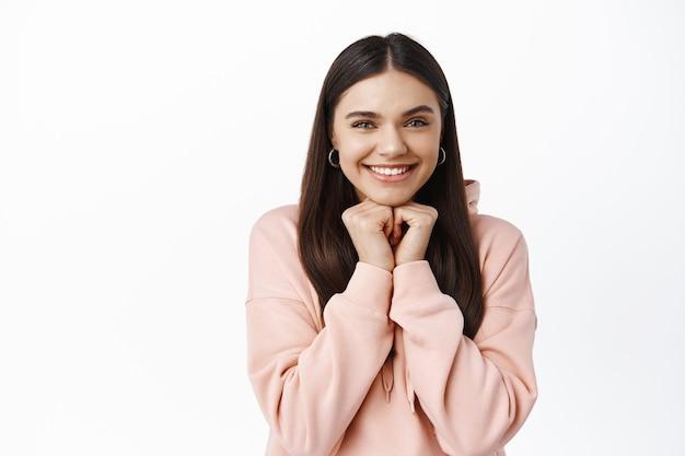 かわいい笑顔のブルネットの少女の肖像画、手に寄りかかって、何か興味のあるものを見て、正面を驚かせて見つめ、白い壁で楽しませて立っている