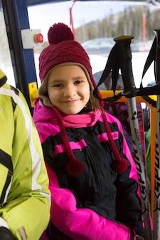 Портрет милой улыбающейся девушки, держащей лыжные палки