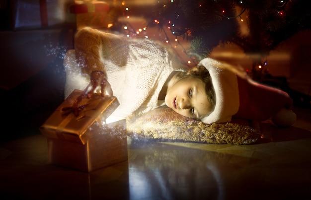 床に横たわって、魔法の光る箱の中を見ているかわいい笑顔の女の子の肖像画