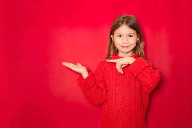 彼女の手で兆候を示すかわいい笑顔の女の子の肖像画