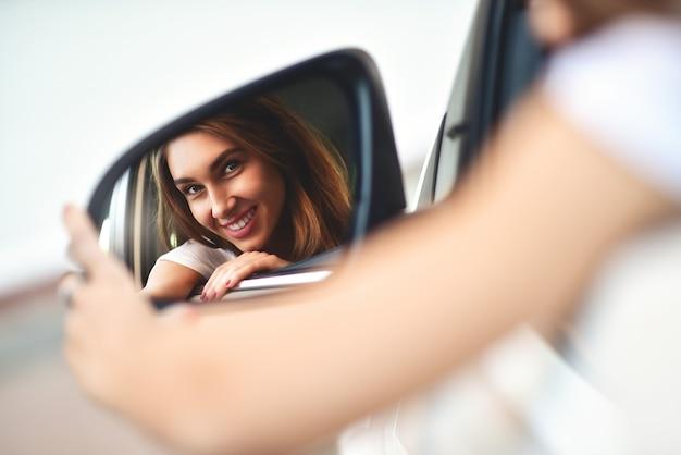 귀여운 웃는 소녀의 초상화는 .car에 앉아서 자동차 거울을 봅니다.