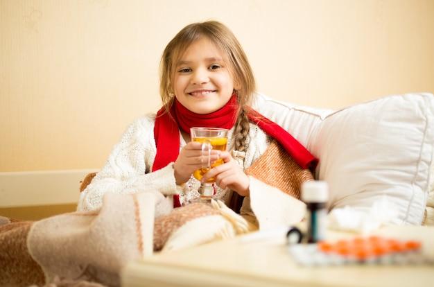 ベッドに座って熱いお茶を飲むかわいい笑顔の女の子の肖像画