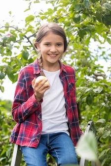 Портрет милой улыбающейся девушки, сидящей на стремянке и кусающей свежее яблоко