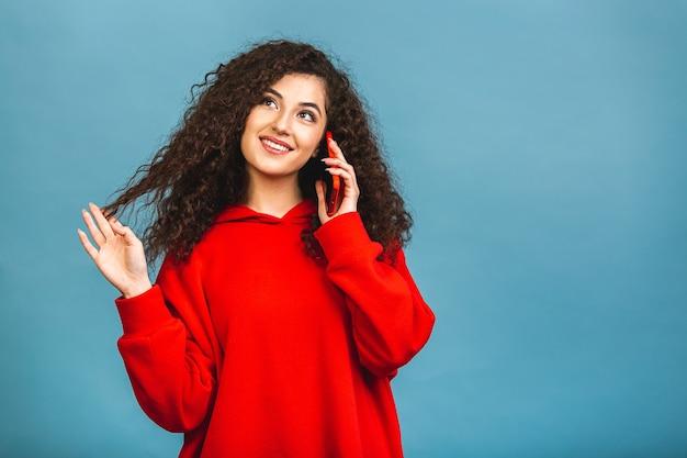 Портрет милой улыбающейся счастливой молодой радостной женщины с вьющейся прической, носящей вскользь, разговаривая по мобильному телефону, изолированному на синем фоне.